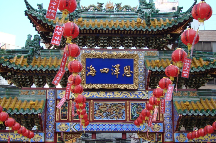 Lanterns hang in front of a Chinatown gate