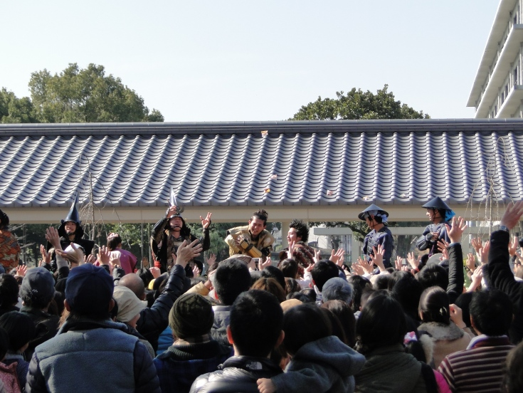 Costumed characters at Kumamoto Castle fling beans into the crowd