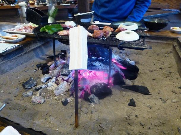 Tofu cooks on a skewer in the irori
