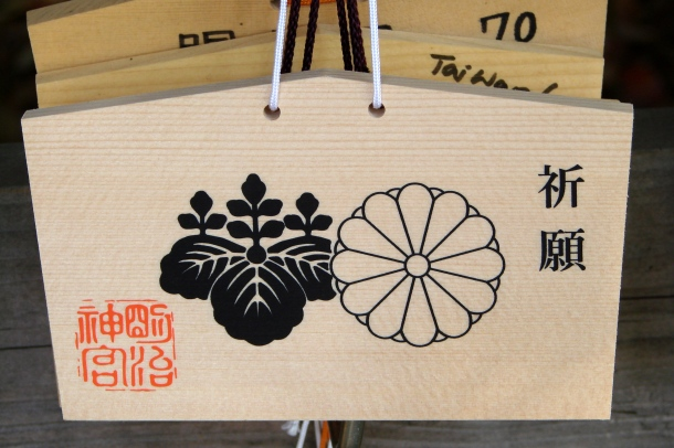 A prayer plaque bearing the government's paulownia crest and the chrysanthemum mon of the Imperial Family