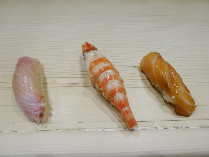 Nigiri sushi put right on the bar between chef and  diner, already brushed with soy sauce.
