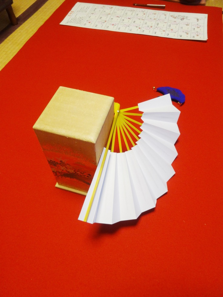 A lucky throw, with the fan leaning against the makura