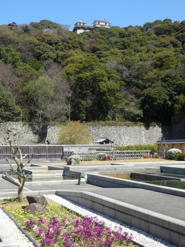 View of the castle on the hill from the Ninomaru Shiseki Garden