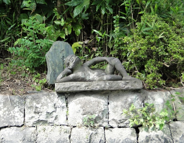 A kappa lounges on a riverbank in Yanagawa